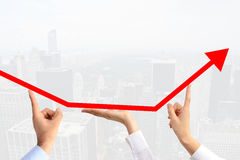 Teamwork concept suggested by three business people's hands guiding an arrow graph chart to go upwards Royalty Free Stock Photos