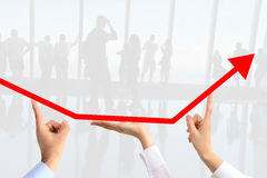 Teamwork concept suggested by three business people's hands guiding an arrow graph chart to go upwards Stock Image