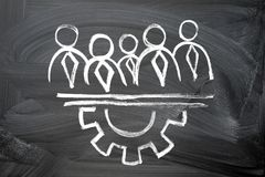 Teamwork concept. Chalk drawing on a blackboard of businessmen silhouettes and gear semicircle royalty free stock image