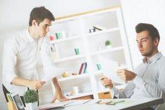 Teamwork concept. Two attractive young caucasian gentlemen doing paperwork in modern office Stock Image