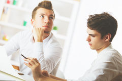 Teamwork concept. Two attractive young caucasian guys doing paperwork in modern office Stock Images
