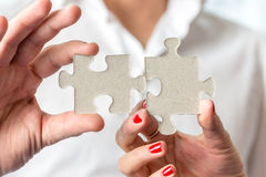 Teamwork concept using two puzzle pieces being fitted together b Royalty Free Stock Photography