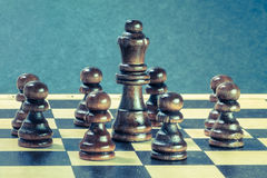 Teamwork concept with wooden chess pawns  nd chess queen. Stock Photography