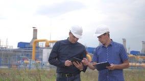 teamwork concetto della stazione di produzione del gas di industria video di movimento lento due ingegneri in caschi stanno studi video d archivio