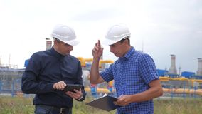 teamwork Concetto della stazione di produzione del gas di industria video di movimento lento Due ingegneri in caschi stanno studi archivi video