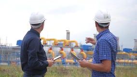 teamwork concetto della stazione di produzione del gas di industria video di movimento lento due ingegneri in caschi stanno studi stock footage