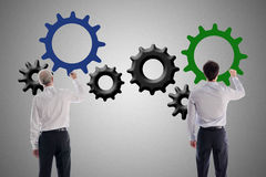 Teamwork and contribution concept. Businessmen drawing gear wheels Stock Photo
