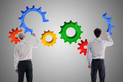 Teamwork and contribution concept. Businessmen drawing gear wheels on gray background Royalty Free Stock Image