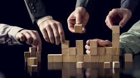 Teamwork and cooperation concept. Five male hands building a structure of wooden blocks on black desk with reflection, toned retro effect Stock Photos