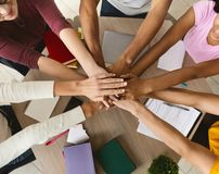 Multi ethnic group of students joining hands together in cooperation