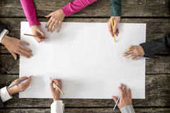 Teamwork and cooperation concept. Top view of six people - men and women - drawing or writing on a large white blank sheet of paper Royalty Free Stock Photography