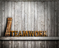 Teamwork cooperation concept. Word text and bundle of wood on wooden background Stock Image