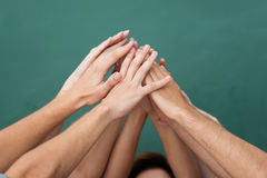 Teamwork and cooperation. With a group of young people all raising their hands together and forming an overlapping pyramid, closeup view of their arms and hands Stock Photography