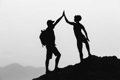Teamwork couple celebrate reaching life goal success. Successful couple teamwork achievement climbing or hiking, business concept with men and women celebrating Stock Photos