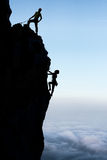 Teamwork couple climbers in silhouette stock photo