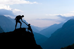 Teamwork couple climbing helping hand. Teamwork couple helping hand trust assistance silhouette in mountains, sunset. Team of climbers men and women hiker, help Royalty Free Stock Photography