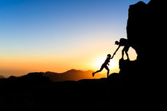 Teamwork couple climbing helping hand. Teamwork couple helping hand trust help silhouette in mountains, sunset. Team of climbers man and woman hikers, help each stock photo