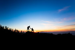 Teamwork couple climbing helping hand. Teamwork couple helping hand trust help silhouette in mountains, sunset. Team of climbers men and women hikers, help each royalty free stock photography