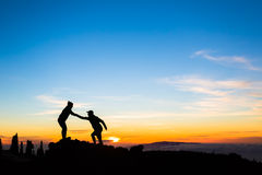 Teamwork couple climbing helping hand. Teamwork couple helping hand trust help silhouette in mountains, sunset. Team of climbers men and women hikers, help each stock image