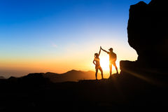 Teamwork couple climbing helping hand. Teamwork couple helping hand trust help, silhouette success in mountains. Team of climbers men and woman. Hikers celebrate stock photos