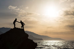 Teamwork couple climbing hiking with helping hand. Teamwork couple helping hand trust help silhouette in mountains on sunrise. Team of climbers men and women Stock Image