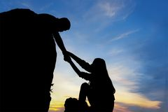 Teamwork couple helping hand trust assistance silhouette in mountains, sunset. royalty free stock photography