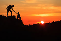 Teamwork couple helping hand trust in inspiring mountains. Teamwork couple helping hand trust silhouette in inspiring mountains. Team of climbers assistance men royalty free stock photo