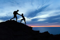 Teamwork couple hikers silhouette in mountains, climbers team. Teamwork couple hiking, help each other, trust assistance and silhouette in mountains, sunset over stock photo