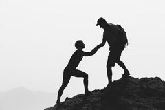 Teamwork couple hiking climbing helping hand. Teamwork couple helping hand, trust, help silhouette in mountains, sunset. Team of climbers men and women hikers stock photo