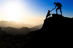 Teamwork couple hiking helping hand. Teamwork couple hiking help each other trust assistance silhouette in mountains, sunset. Team of climbers men and women stock photo