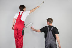 Teamwork from a couple are painting a grey wall Stock Photo