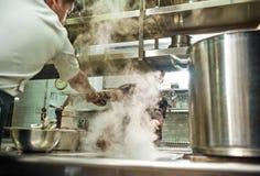 teamwork Cuoco unico del ristorante che dà una smerigliatrice di pepe al suo assistente mentre processo di cottura alla cucina fotografie stock libere da diritti