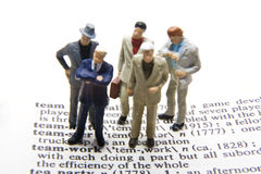 Teamwork Definition. Miniature businessmen with the definition of teamwork Stock Photos