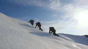Teamwork desire to win. Climbers climb to the top of a snowy mountain in Alaska. travelers in the arctic on a hill in. Bright rays of the sun. Siberia concept royalty free stock images