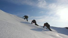 Teamwork desire to win. Climbers climb to the top of a snowy mountain in Alaska. travelers in the arctic on a hill in. Bright rays of the sun. Siberia concept royalty free stock photos
