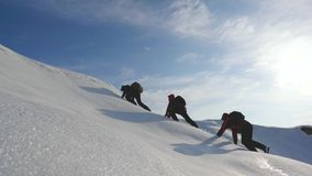 Teamwork desire to win. Climbers climb to the top of a snowy mountain in Alaska. travelers in the arctic on a hill in. Bright rays of the sun. Siberia concept royalty free stock photo