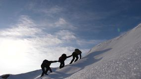 Teamwork desire to win. Climbers derajat each other`s hands to help a friend climb to top of a snowy mountain. travelers. Teamwork desire to win. Climbers stock image