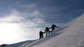Teamwork desire to win. Climbers derajat each other`s hands to help a friend climb to top of a snowy mountain. travelers. Teamwork desire to win. Climbers royalty free stock photography