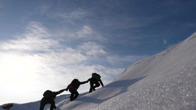 Teamwork desire to win. Climbers derajat each other`s hands to help a friend climb to top of a snowy mountain. travelers. Teamwork desire to win. Climbers royalty free stock photo