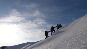 Teamwork desire to win. Climbers derajat each other`s hands to help a friend climb to top of a snowy mountain. travelers. Teamwork desire to win. Climbers royalty free stock image