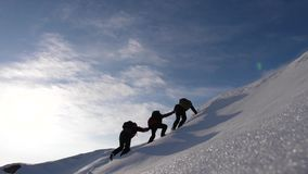 Teamwork desire to win. Climbers derajat each other`s hands to help a friend climb to top of a snowy mountain. travelers. Teamwork desire to win. Climbers royalty free stock photos
