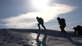 Teamwork desire to win. Climbers on a rope help a friend climb to the top of the hill. Silhouette of travelers in winter. On a hill in the bright rays of sun stock photos