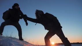 Teamwork-Dienstreiseschattenbildkonzept Zwei Wandererwinterschnee-Touristenbergsteiger klettern zum Lebensstil die Spitze von stock video