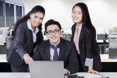 Teamwork discussing with laptop at workplace stock photo