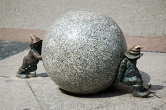 Teamwork dwarfs Wroclaw Poland. Dwarfs moving big and heavy sphere. Small piece of art situated close to the market square in Wroclaw, Poland Royalty Free Stock Photography