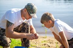 Teamwork. Father and son fishing on a summer weekend. Hobby and sport activity, preparing fish bait.