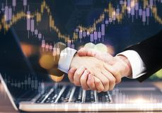 Teamwork and finance concept. Handshake and forex chart on abstract blurry background with laptop. Teamwork and finance concept. Multiexposure stock image