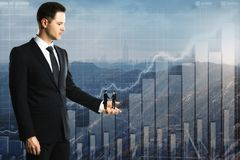 Teamwork and finance concept. Side view of european businessman holding two tiny subordinated shaking hands on abstract city with business chart background Royalty Free Stock Image