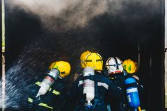 Teamwork Of Firefighters Training Stock Photos