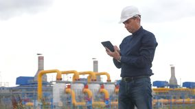 Teamwork gas production station concept. Engineering man standing with digital tablet white safety helmet. man engineer. In helmet work at the station are stock video footage